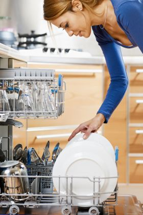 Woman putting dishes in a dishwasher